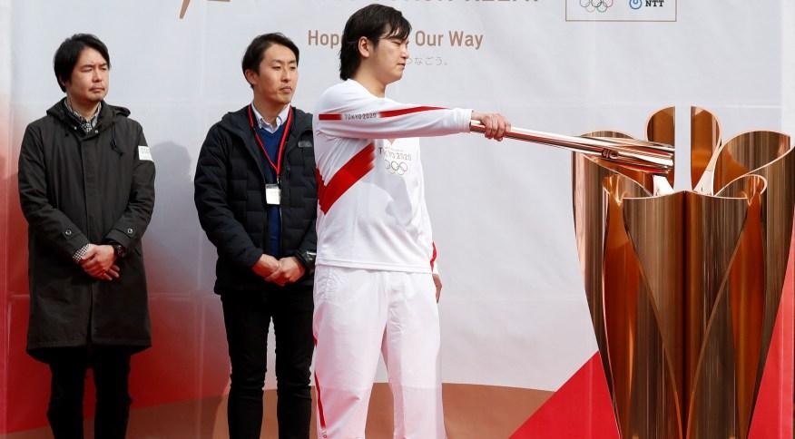 Homem ensaia o revezamento da tocha dos Jogos Olímpicos de Tóquio