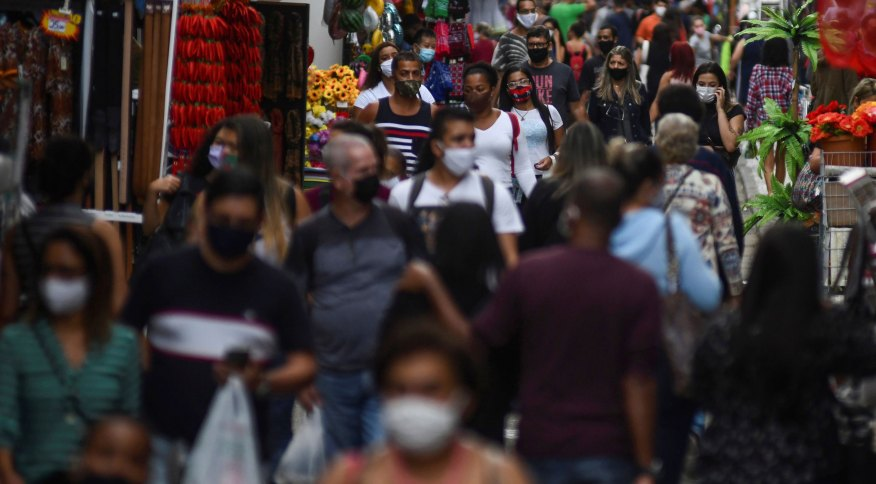 Pessoas circulam de máscara por rua de comércio popular no centro do Rio de Janeiro durante pandemia da Covid-19