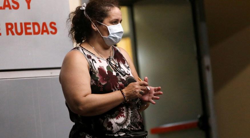 Mulher usa máscara em hospital de Buenos Aires após confirmação da morte por coronavírus