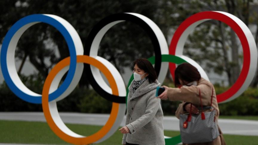 Pedestres caminham em frente a museu olímpico em Tóquio