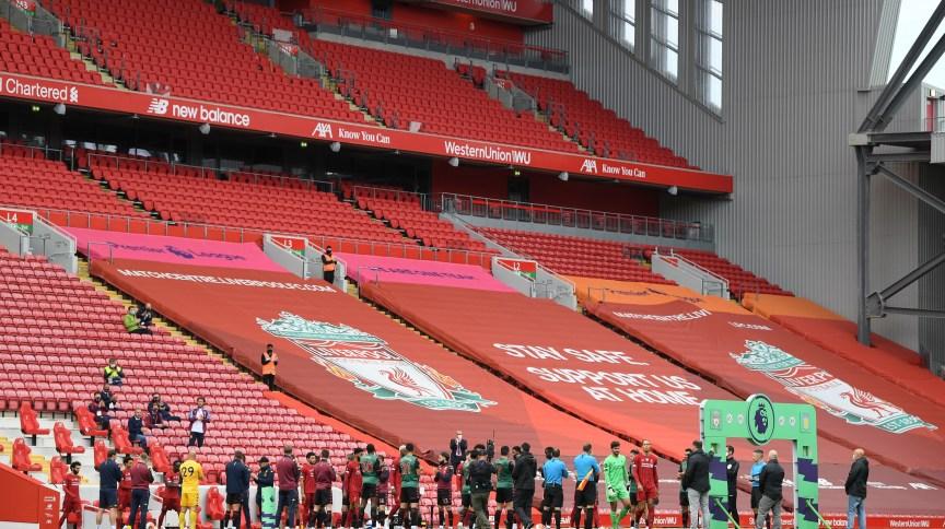 Estádio Anfield com arquibancadas vazias durante aquecimento de jogadores do Liverpool