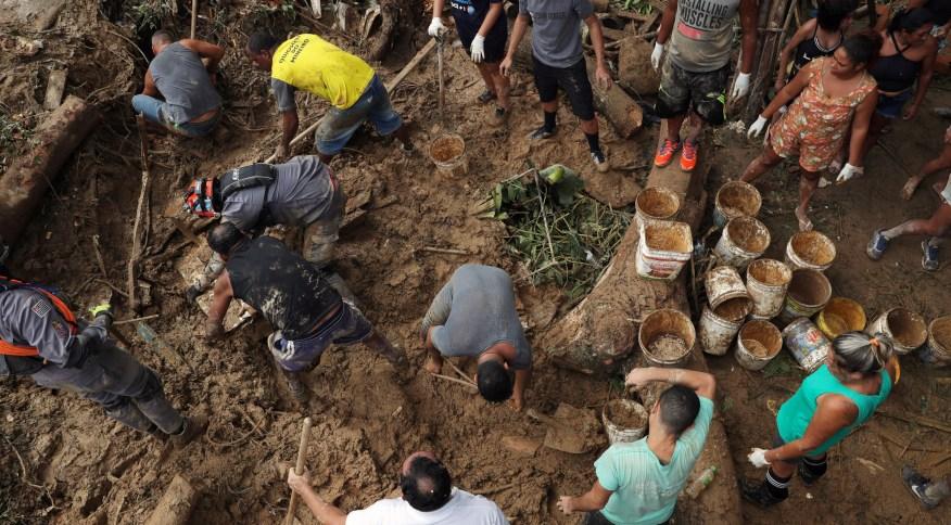 Voluntários e bombeiros trabalham nas buscas por desaparecidos no morro da Barreira do João Guarda, no Guarujá (SP)