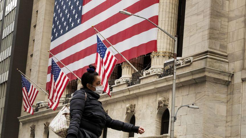 Pedestre caminha de máscara em frente à Bolsa de Valores de Nova York