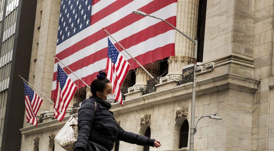 Pedestre caminha de máscara em frente à Bolsa de Valores de Nova York: ações sobem nos EUA