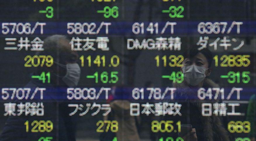 Com máscara de proteção ao novo coronavírus, homem observa painel com índices de ações, em Tóquio,, no Japão (10.mar.2020)