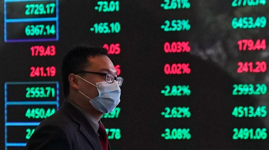 Homem de máscara caminha pela Bolsa de Xangai (28.fev.2020)