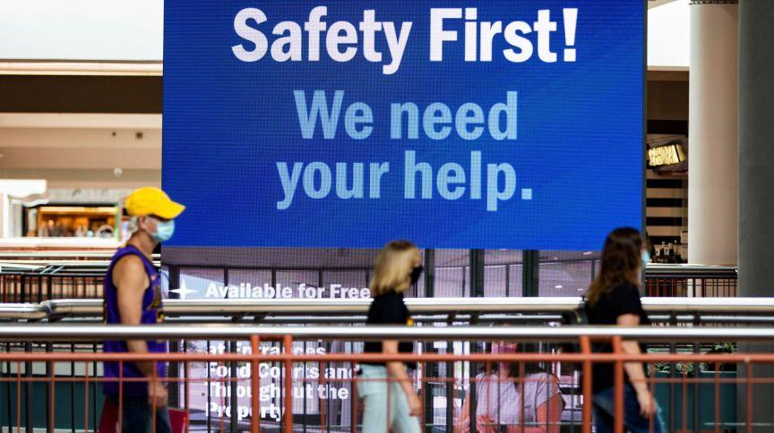 """Pessoas caminham de máscara em shopping no estado de Nova York; atrás, a placa diz """"Segurança em primeiro lugar! Precisamos de sua ajuda"""""""