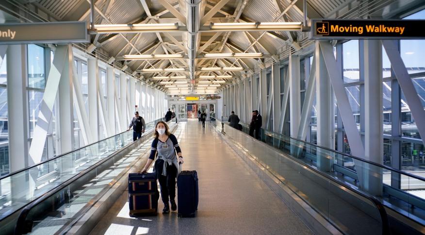 Mulher com máscara caminha no aeroporto John F. Kennedy, em Nova York