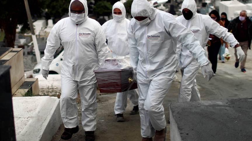 Funcionários de cemitério com roupa de proteção durante enterro de vítima da Covid-19 em Nova Iguaçu (RJ)