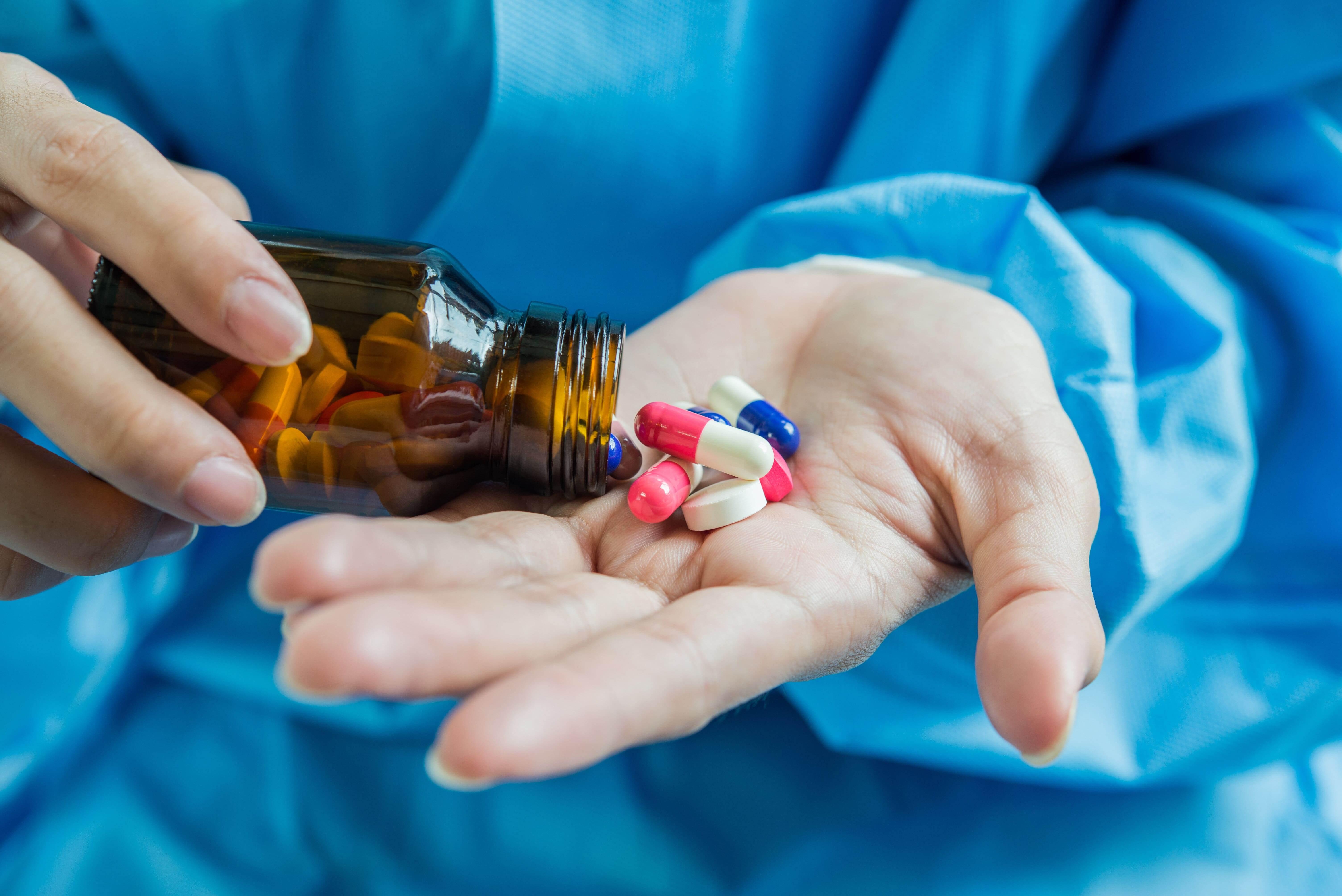 Pessoa virando um frasco de remédios