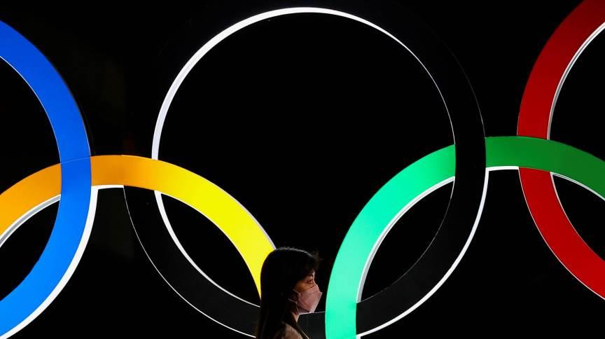Mulher passa pelos anéis olímpicos em Tóquio