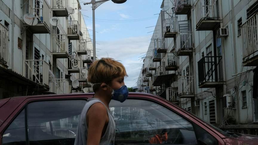 Menino usa máscara de proteção na favela de Manguinhos, no Rio de Janeiro