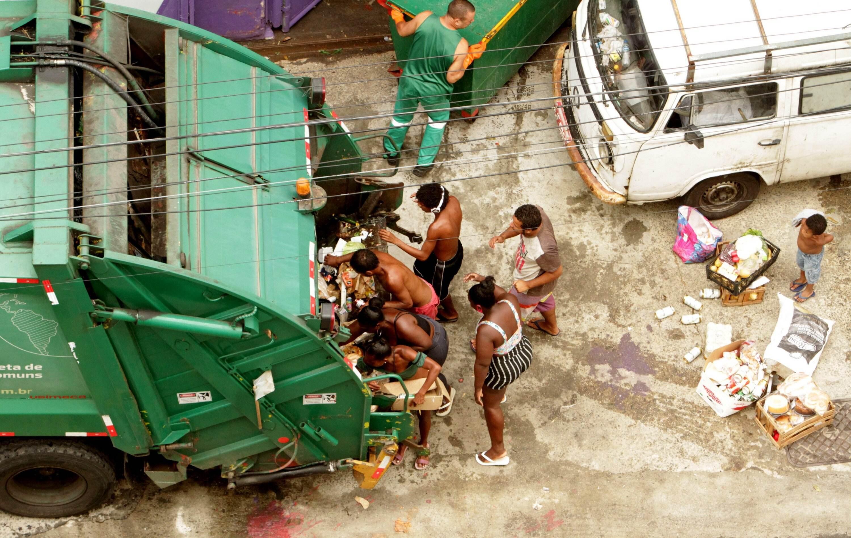 Moradores do Rio tentam encontrar alimentos em caminhão de lixo