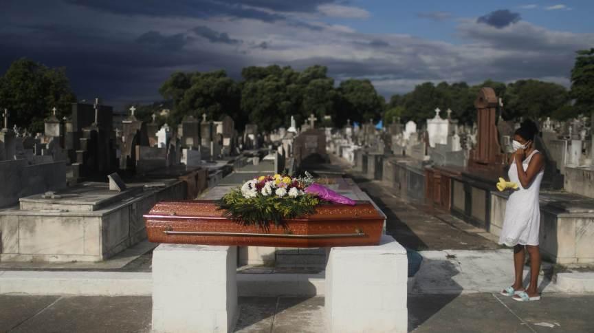 Mulher acompanha enterro da mãe, que morreu de Covid-19, em cemitério do Rio de Janeiro