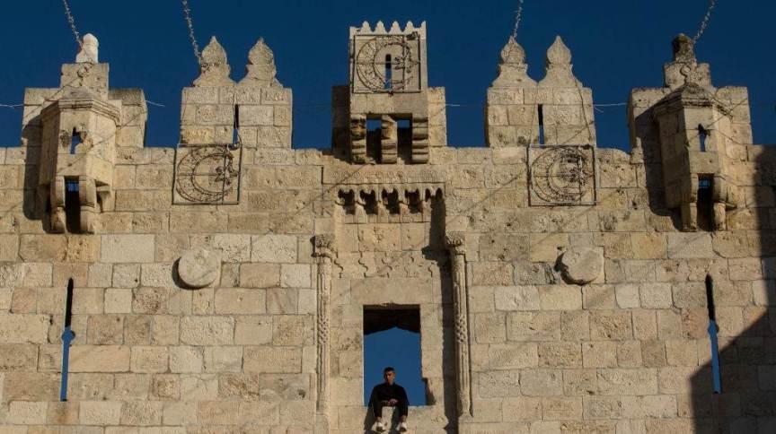 Muçulmano observa a movimentação na cidade velha de Jerusalém sentado no Portão de Damasco