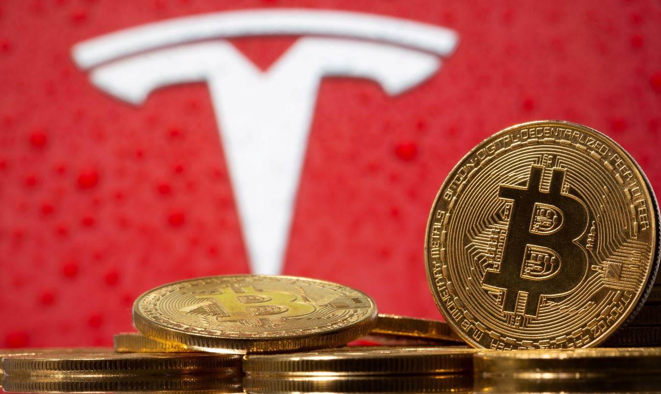 Representação da moeda virtual bitcoin, com logotipo da Tesla ao fundo