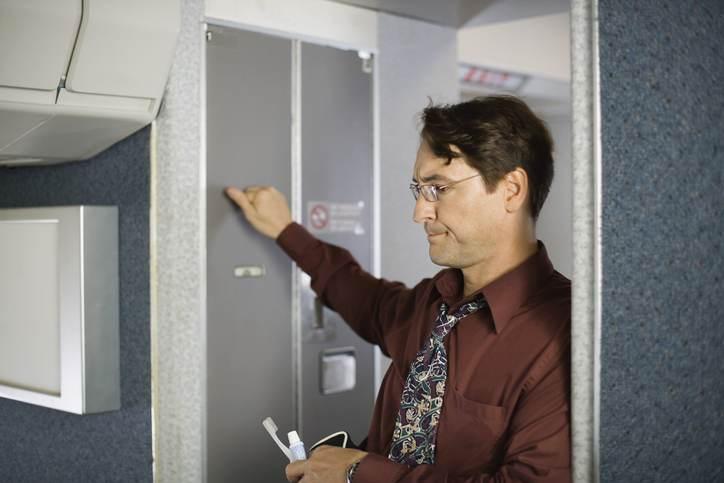 Passageiro na fila para usar banheiro de um avião