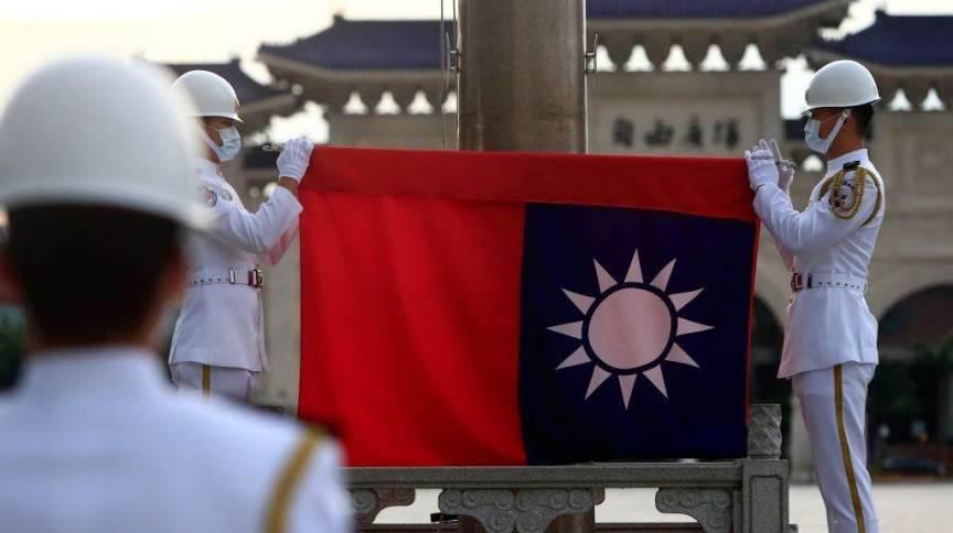 Guardas de Taiwan seguram bandeira em praça de Taipei; discussão sobre soberania da ilha causa atritos com a China