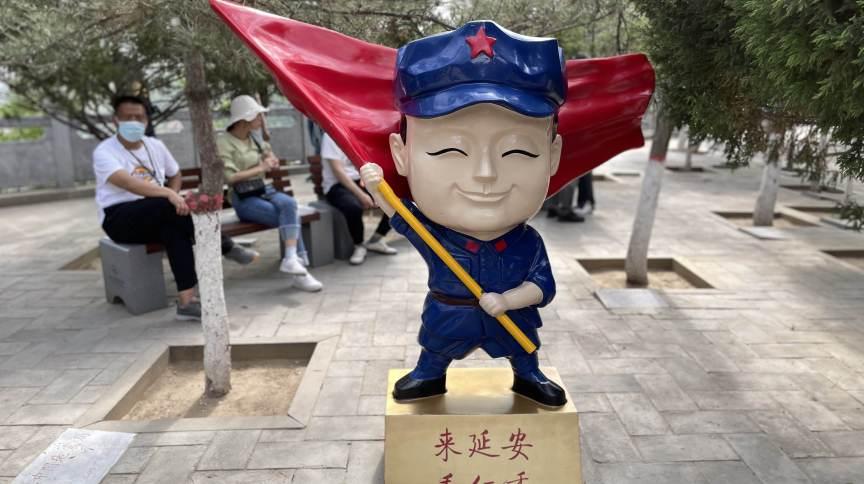 """Personagem de desenho animado em Yan'an, um """"local vermelho"""" na província de Shaanxi, no norte, que anuncia um espetáculo teatral sobre os primeiros dias do Partido Comunista"""