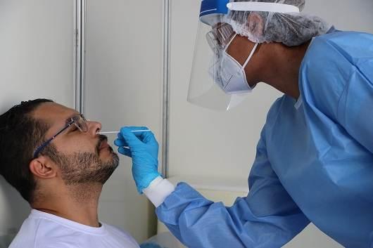 Profissional da Fiocruz realiza teste PCR da Covid-19 em morador