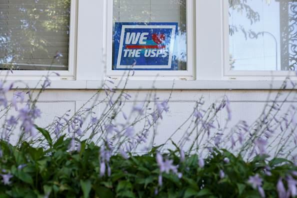 """Placa com a frase """"nós amamos o USPS"""" é vista na janela de uma residência em Det"""