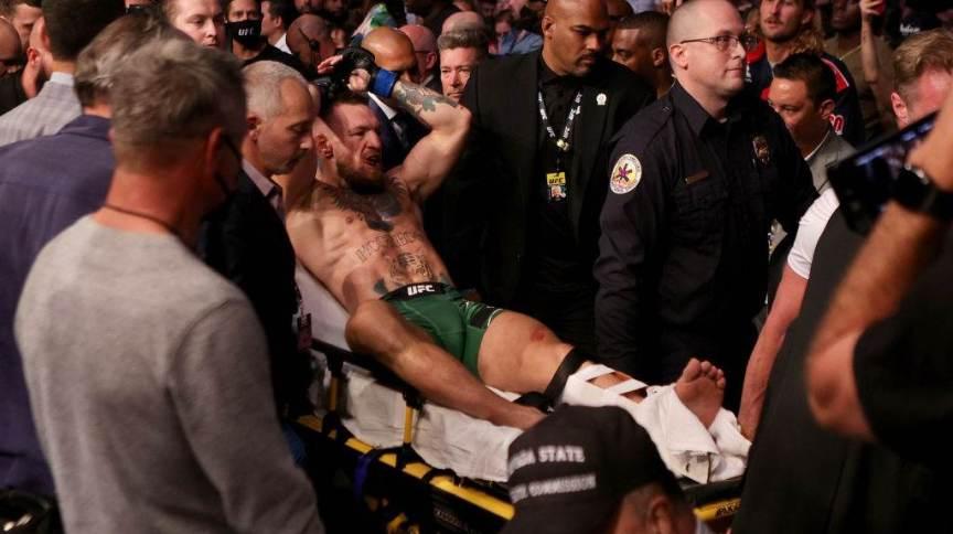 Lutador de UFC Conor McGregor sai do ginásio carregado após quebrar a perna