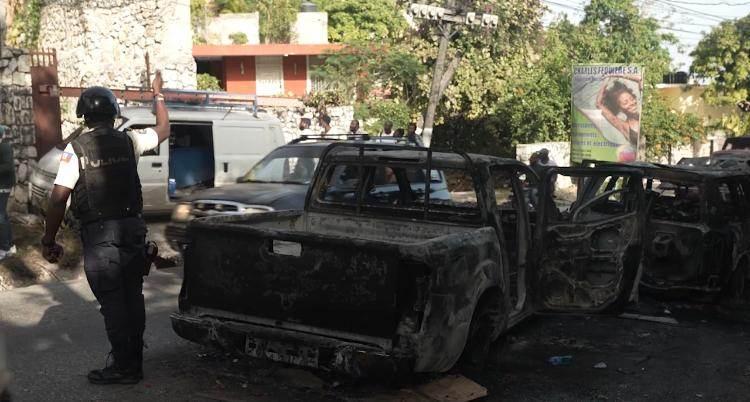 Carros incendiados de supostos mercenários no distrito de Petion-Ville, em Porto