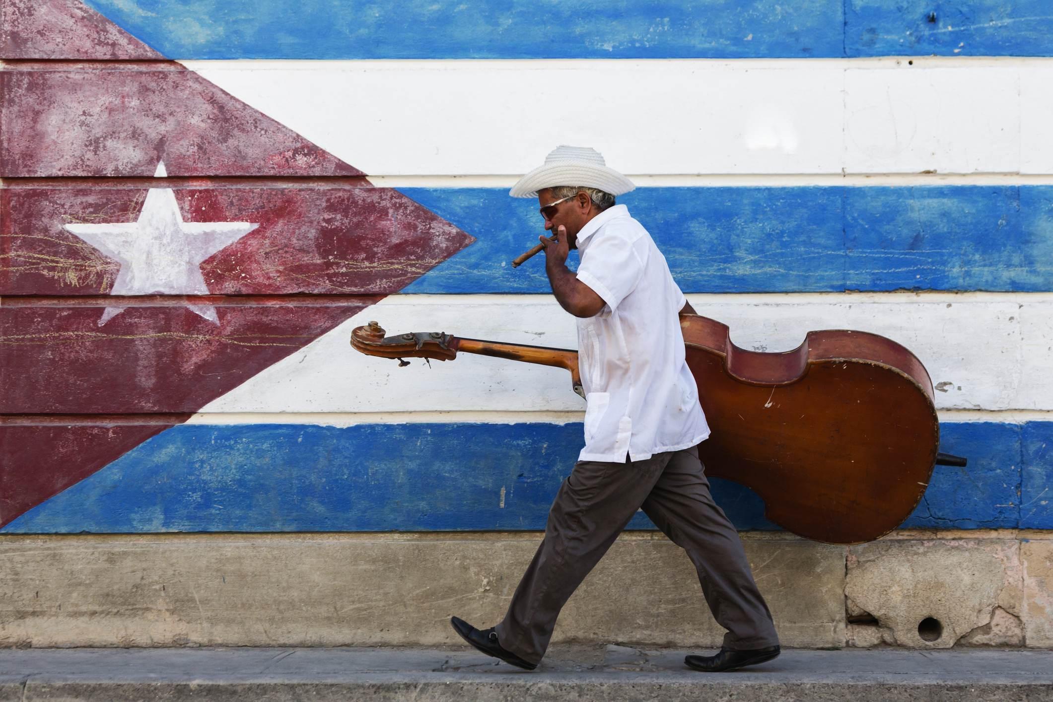 Músico cubano caminha com seu instrumento musical diante de um mural com a bande