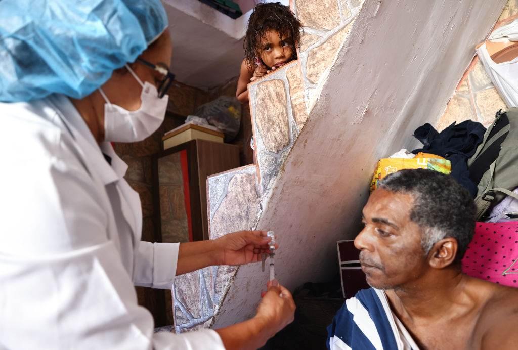 Enfermeira do SUS aplica vacina em homem em sua casa na Rocinha