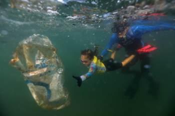 Ao lado do pai, Nina Gomes retira resíduos do oceano com o objetivo de preservar a vida marinha