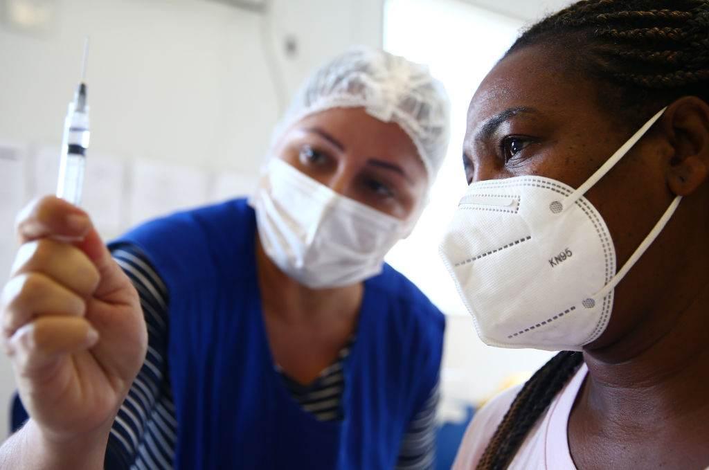 Enfermeira mostra vacina para mulher no Rio de Janeiro