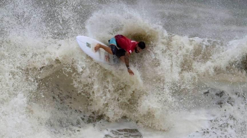 O brasileiro Ítalo Ferreira surfa onda durante as semifinais da competição masculina de surfe nos Jogos Olímpicos