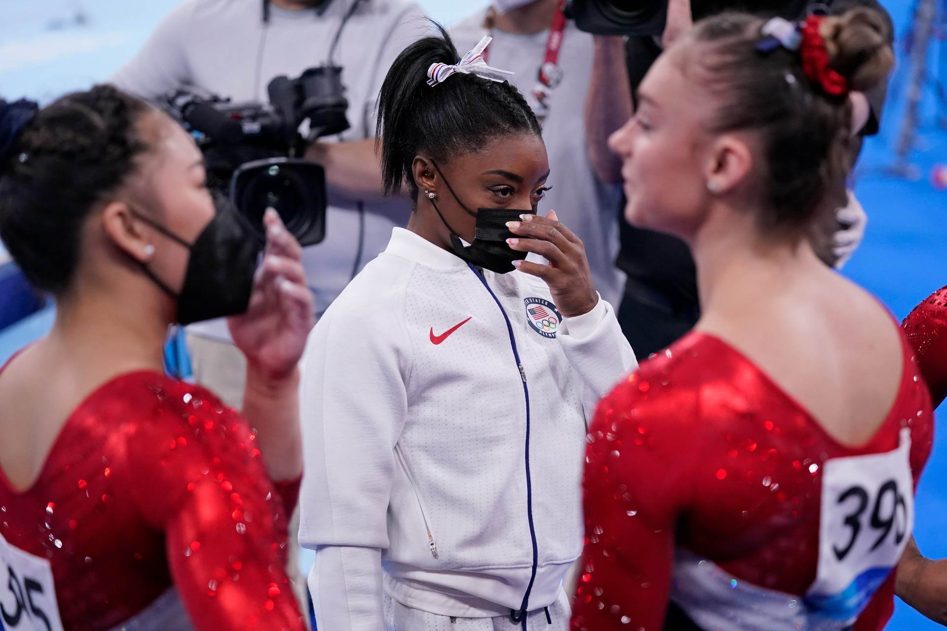 Simone Biles (de máscara) ao lado das outras ginastas dos EUA nas Olimpíadas