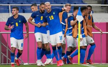 Seleção faz 3 a 1, com dois gols de Richarlison, fica em primeiro lugar no grupo D e avança nos Jogos; na terceira posição, Alemanha é eliminada