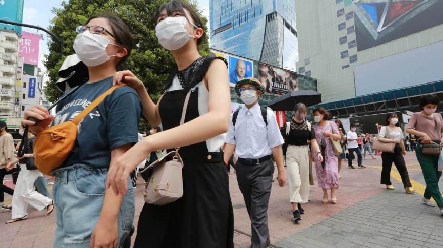 Com máscaras de proteção, japoneses caminham por rua de Tóquio