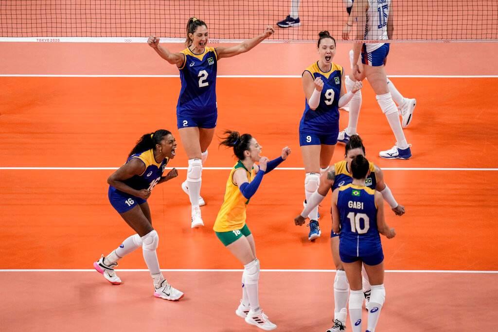 Jogadores do vôlei feminino do Brasil comemoram ponto se abraçando na quadra