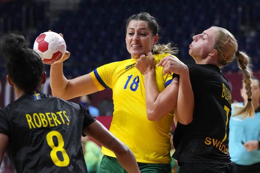 Eduarda segura a bola entre duas jogadoras da Suécia de handebol