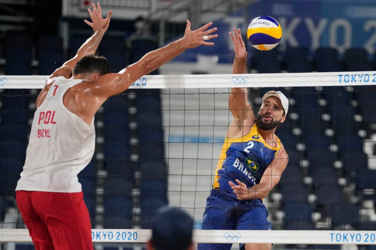 Bruno Schmidt, jogador de vôlei de praia, ataca bola contra polonês Michal Bryl