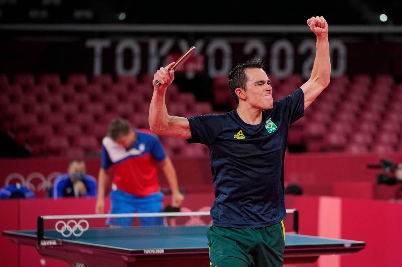 Hugo Calderano vibra com os braços erguidos após vitória no tênis de mesa
