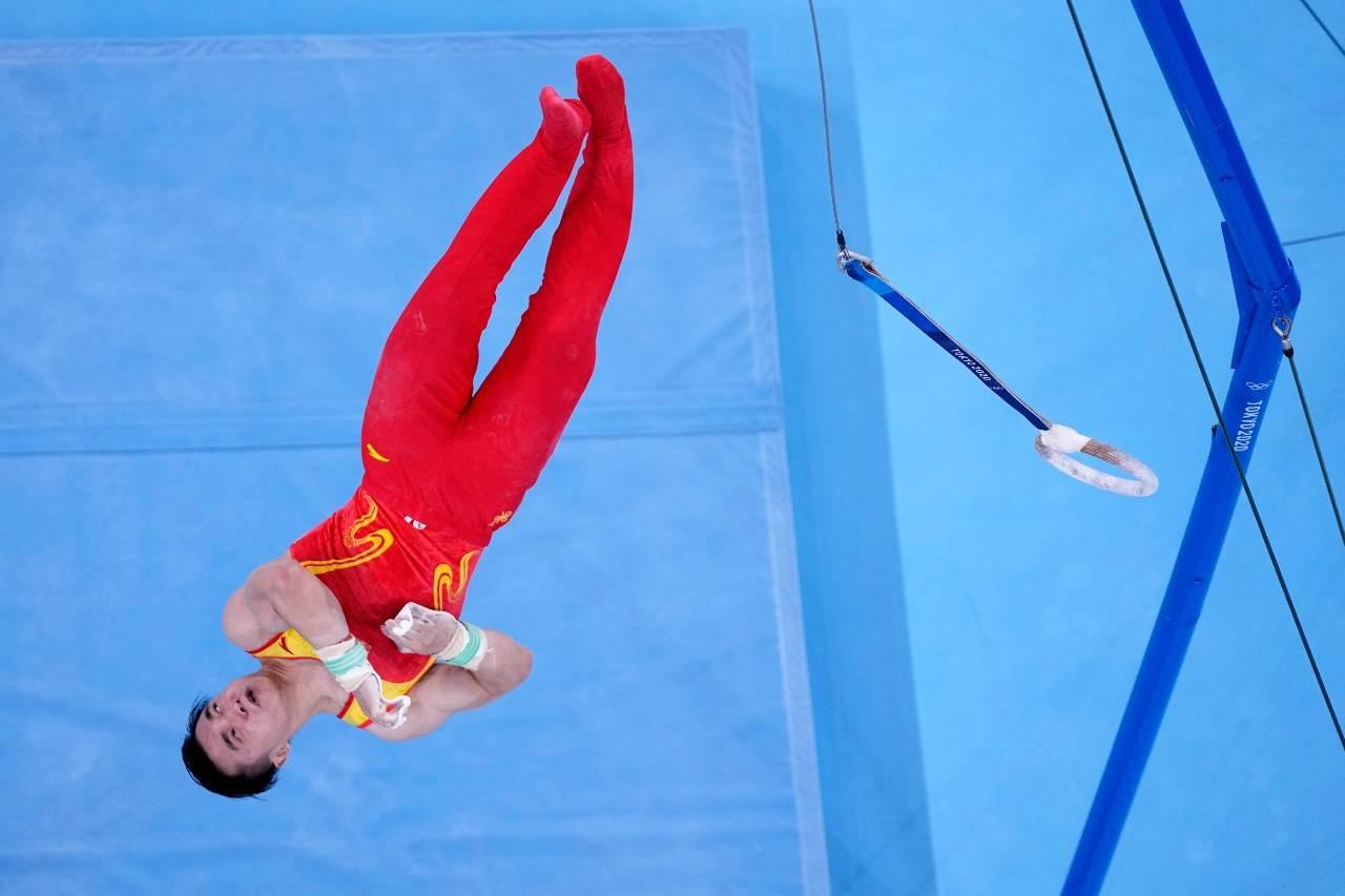 Ginasta chinês Liu Yang de ponta cabeça dando salto mortal na saída das argolas