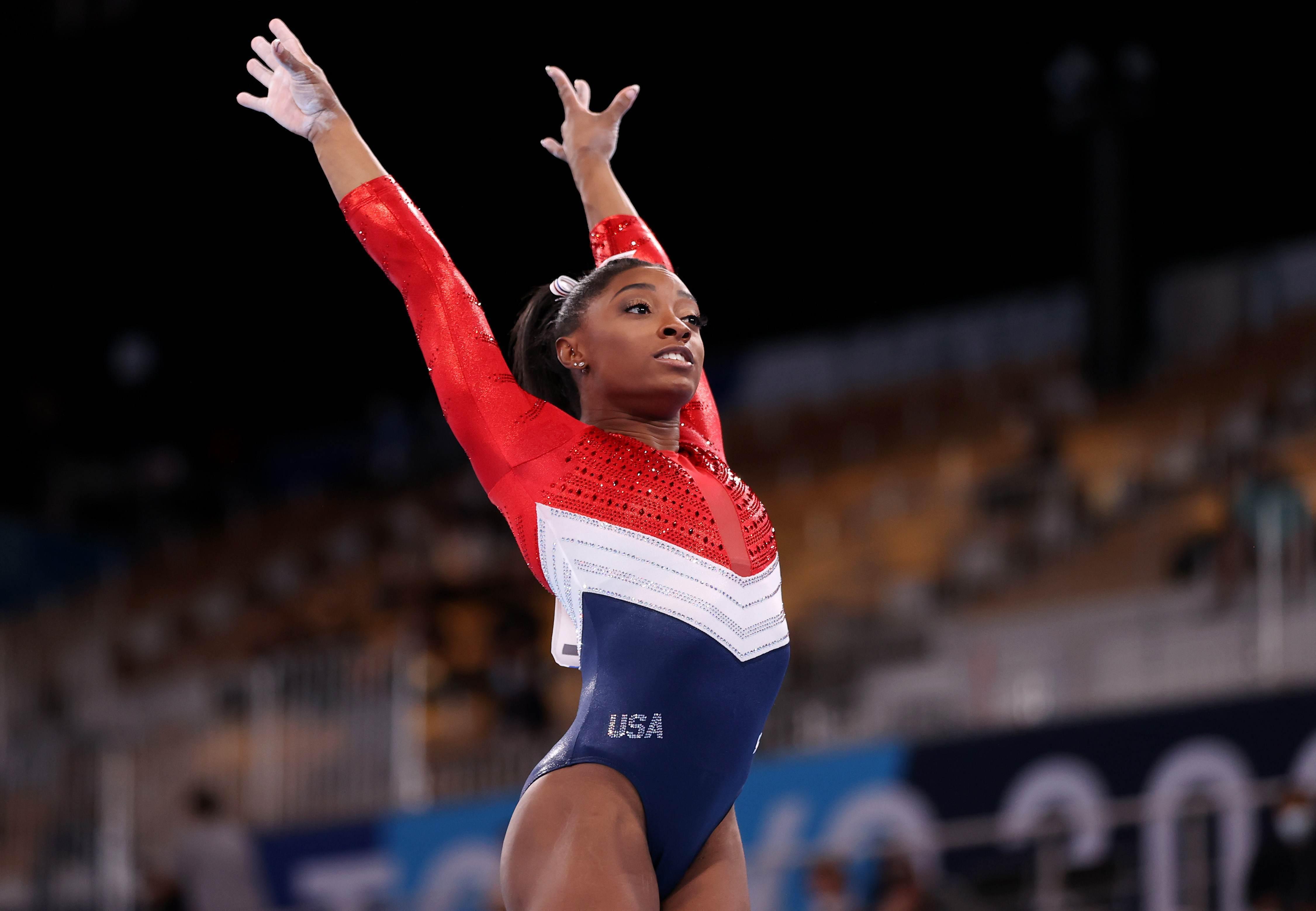 Ginasta dos EUA Simone Biles com os braços para o alto após finalizar exercício