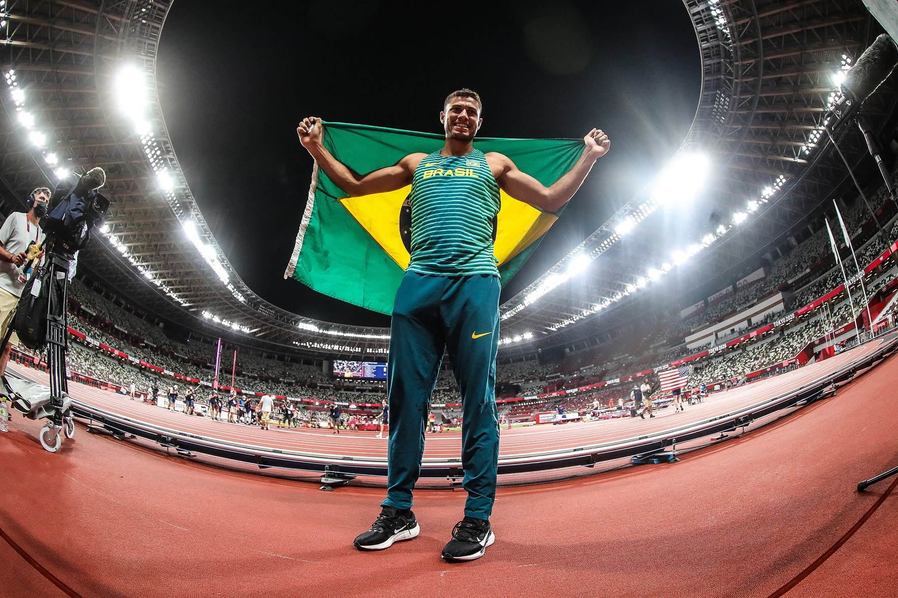 Thiago Braz com a bandeira brasileira após ficar com o bronze no salto com vara
