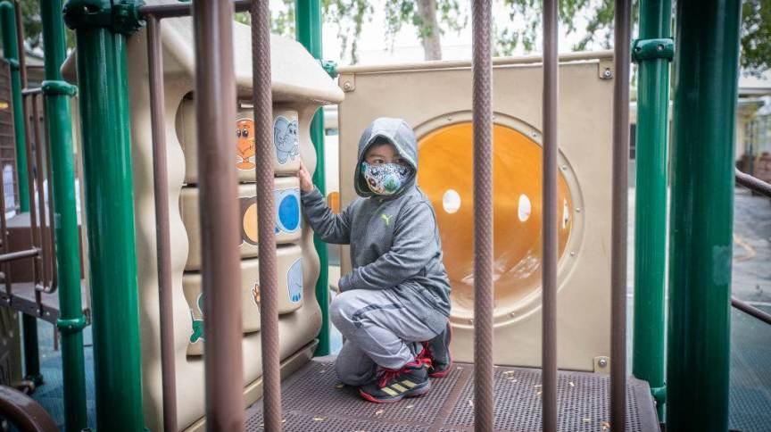 Criança com máscara em parque de Los Angeles, EUA