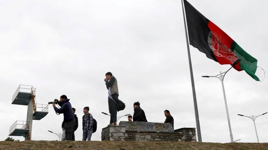 Pessoas tiram fotos ao lado da bandeira afegã em Cabul, Afeganistão
