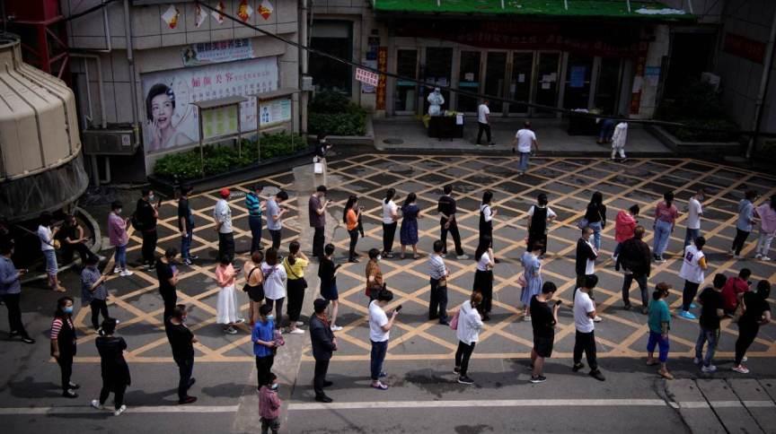 Moradores fazem fila para serem testados em Wuhan, na China