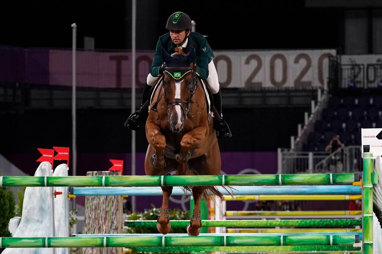 Atleta brasileiro do hipismo em cima do cavalo saltando obstáculo no Japão