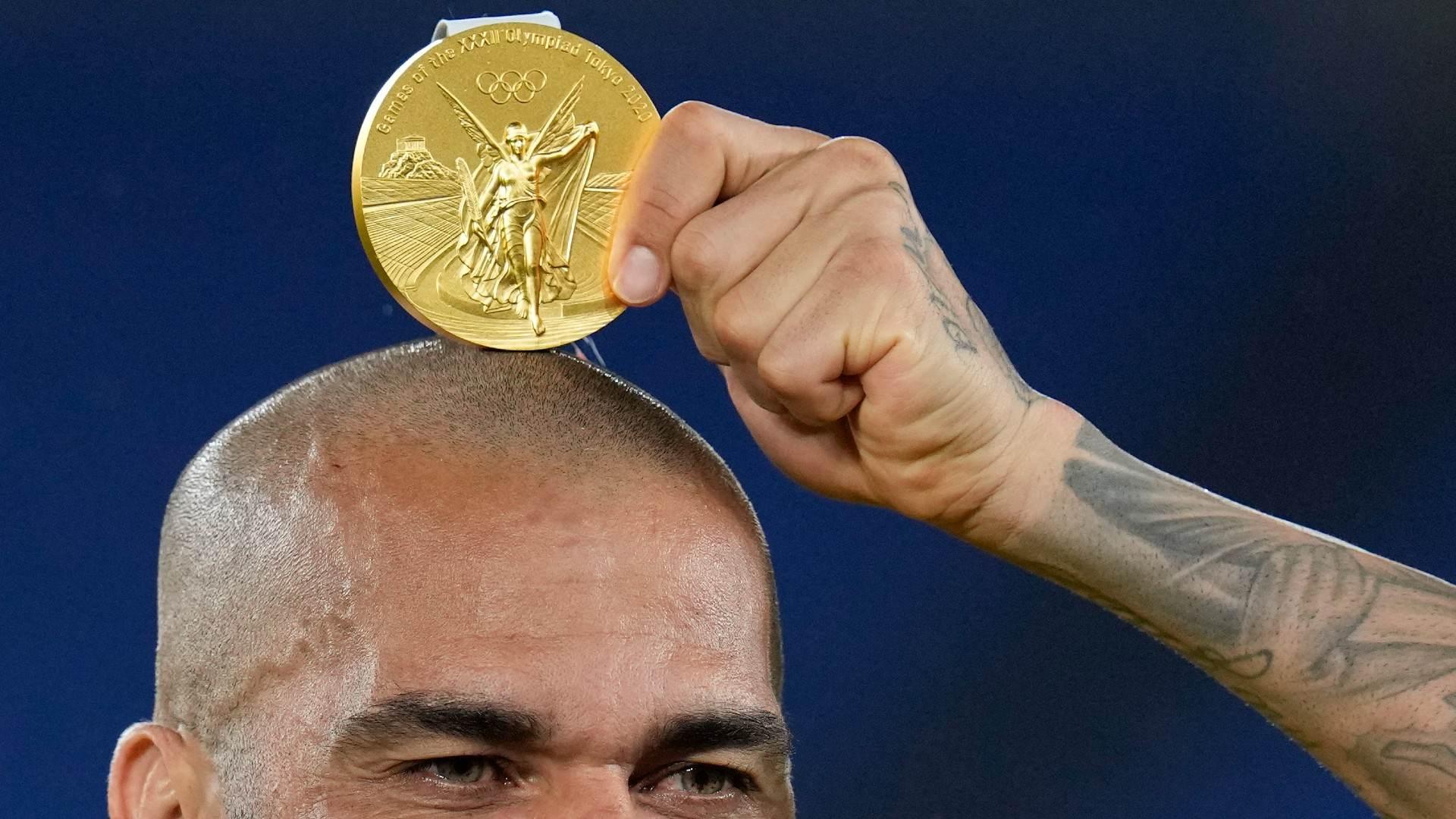 Dani Alves tira foto com medalha de ouro sobre a cabeça após conquista olímpica