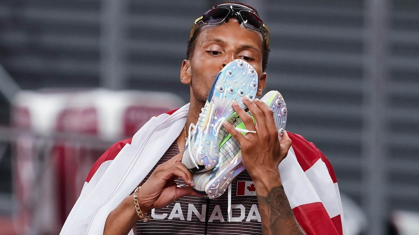 Andre De Grasse, do Canadá, beija seus sapatos após a vitória nos 200 metros