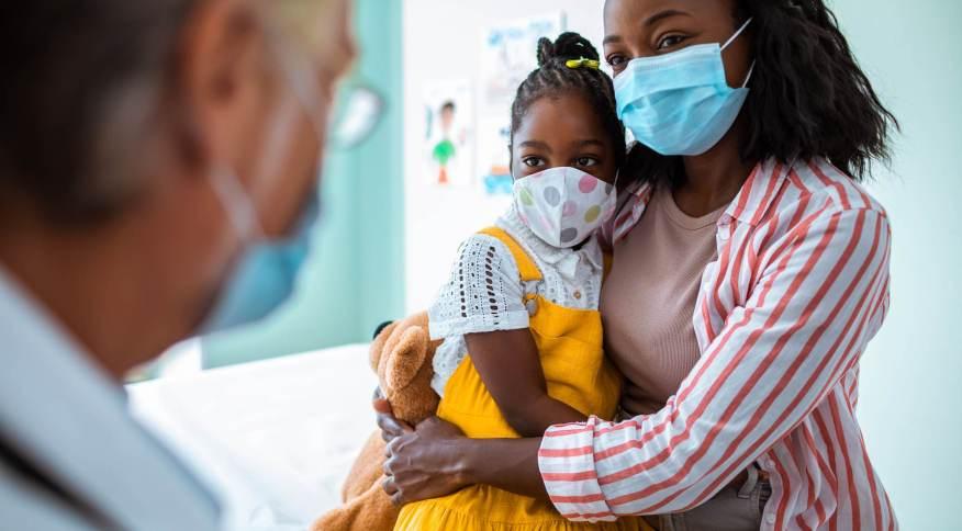 Criança e mãe usam máscaras durante consulta médica