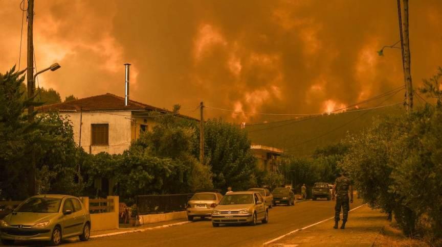 Chamas cercam aldeia de Gouvesi, na ilha de Evia, na Grécia, durante incêndio florestal que atinge diversas regiões do país